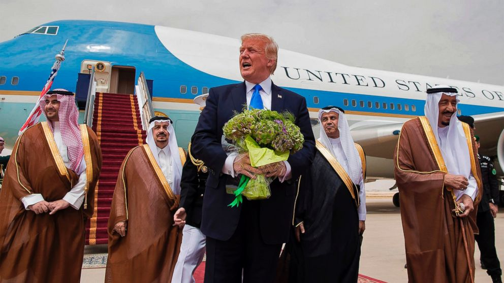 President Donald Trump holds a bouquet of flowers upon being welcomed by Saudi King Salman bin Abdulaziz al-Saud during his arrival at the airport in Riyadh on May 20, 2017.