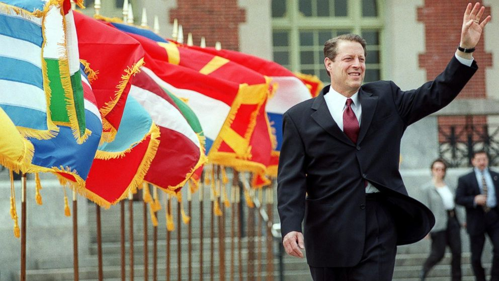 Al Gore waves as he walks past a row of flags at the start of the Commemoration Ceremony of the 50th Anniversary of the North Atlantic Treaty Organization in New York, April 21, 1999.