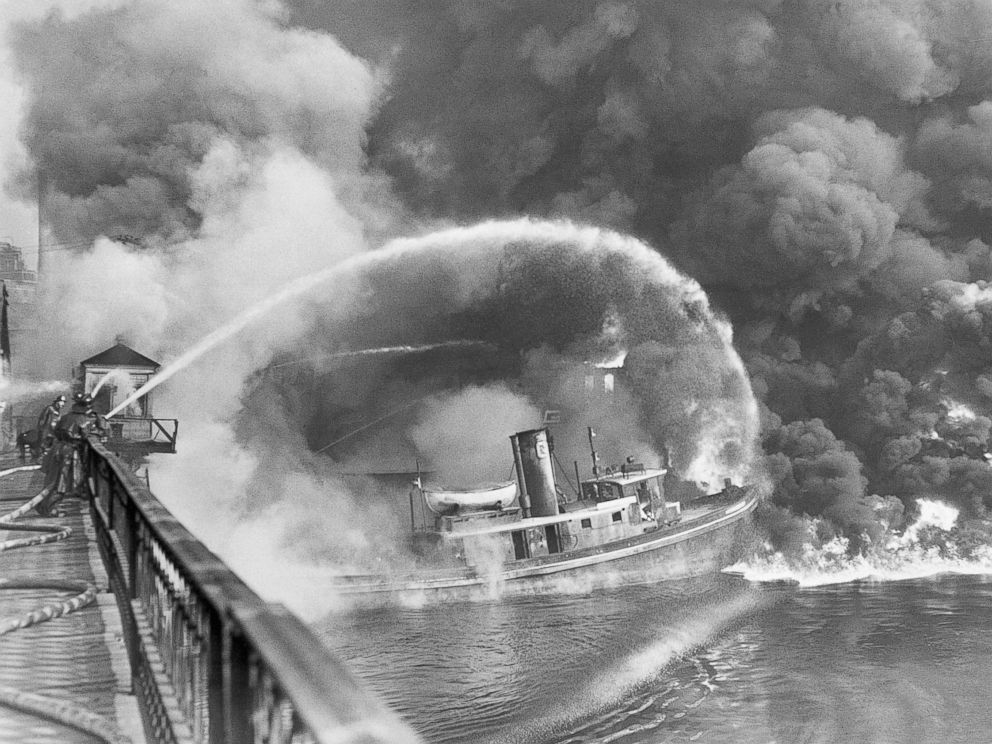 PHOTO: Firemen stand on a bridge over the Cuyahoga River to spray water on a tugboat as a fire burns an oil slick on the river, Nov. 3, 1952. <p itemprop=