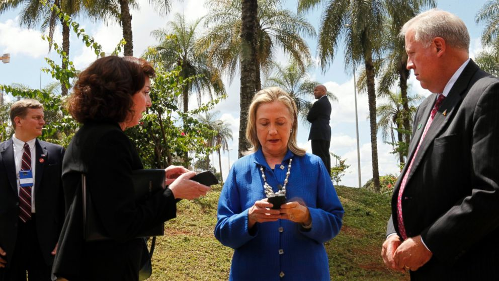 Secretary of State Hillary Rodham Clinton writes on her cell phone with Roberta S. Jacobson, left, and  Thomas Shannon in Brasilia, Brazil,  April 17, 2012.