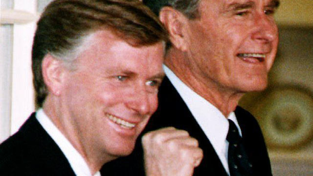 PHOTO: U.S. Vice President Dan Quayle reacts as he and President George Bush walk into the White House in Washington, DC after a welcome home rally 14 October, 1992.