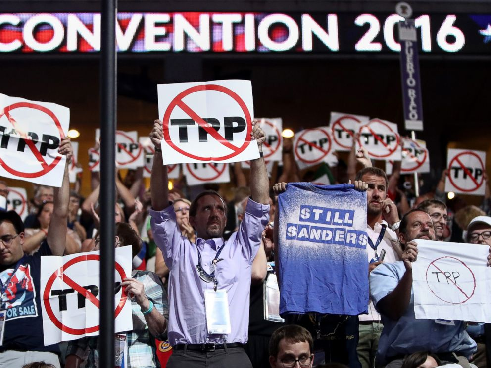 PHOTO: Delegates hold up signs protesting the Trans-Pacific Partnership (TPP) on the first day of the Democratic National Convention at the Wells Fargo Center, July 25, 2016, in Philadelphia.