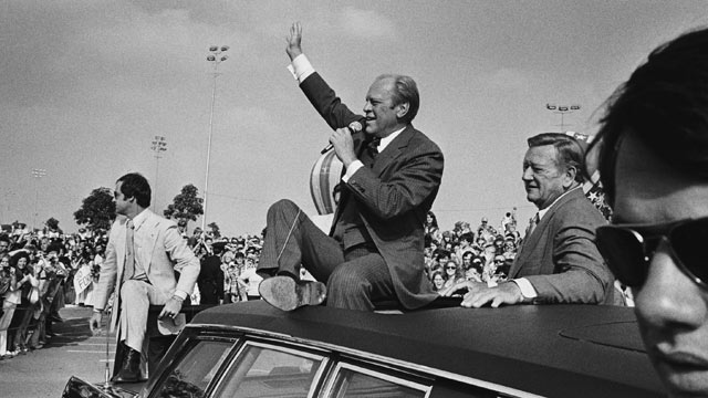 PHOTO: Accompanied by supporter John Wayne, President Ford addresses a crowd from atop his limousine in Orange County, California, during the final stretch of the campaign October 24, 1976 in Fountain Valley, Calif.
