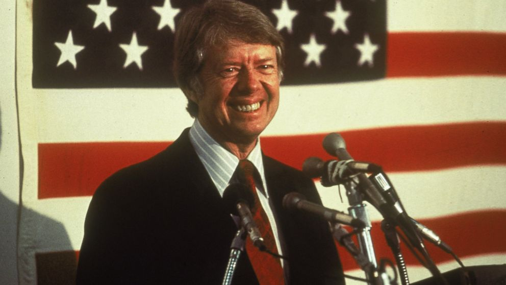 U.S. President Jimmy Carter smiling at a podium in front of an American flag.