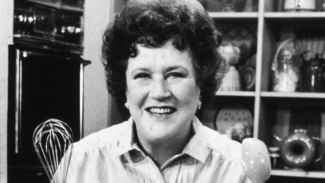 """PHOTO: American chef Julia Child stands in front of a countertop, holding a whisk and a ladle, on the set of her television series, """"The French Chef""""."""