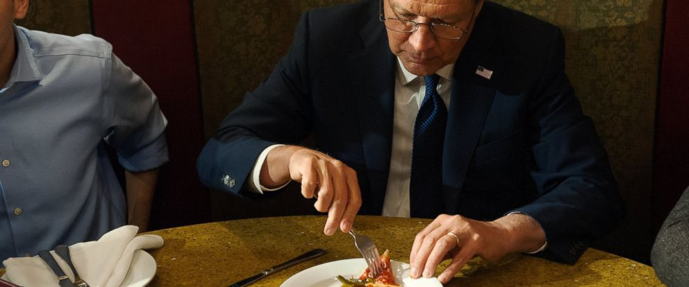 PHOTO: Presidential candidate John Kasich eats a piece of pizza at Ginos Pizzeria and Restaurant on March 30, 2016 in the Queens borough of New York City.