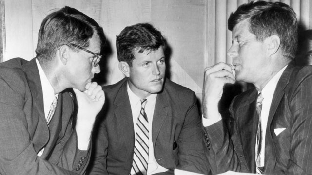 PHOTO: US Attorney General Robert Kennedy, US Senator Edward Kennedy, and US President John F. Kennedy speak while seated behind a desk in this 1962 file photo.