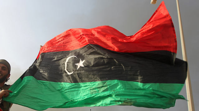 PHOTO: A Libyan National Transitional Council (NTC) fighter waves the Libyan revolution flag in Sirte after fierce fighting against loyalist troops, Oct. 9, 2011.