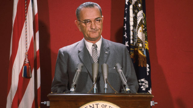PHOTO: American statesman Lyndon Baines Johnson, the 36th President of the United States of America, making an address at a podium flanked by two flags, around 1965.