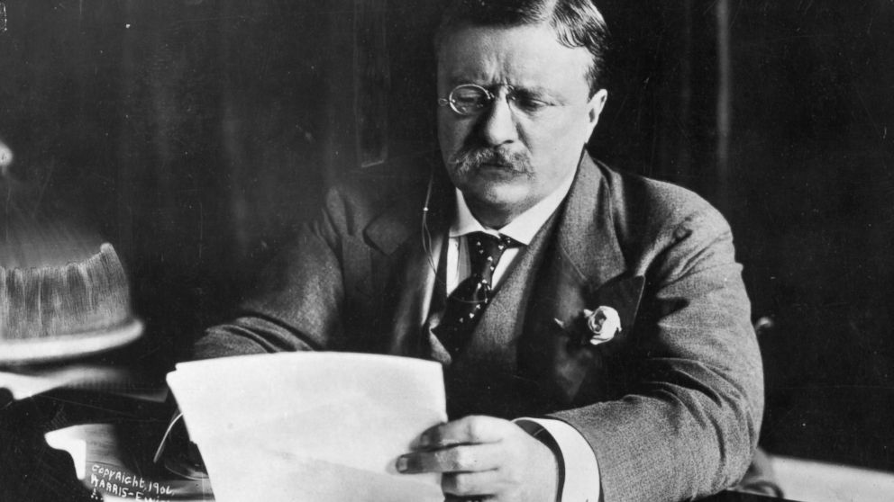 Theodore Roosevelt, the 26th President of the United States, sitting at his desk working.