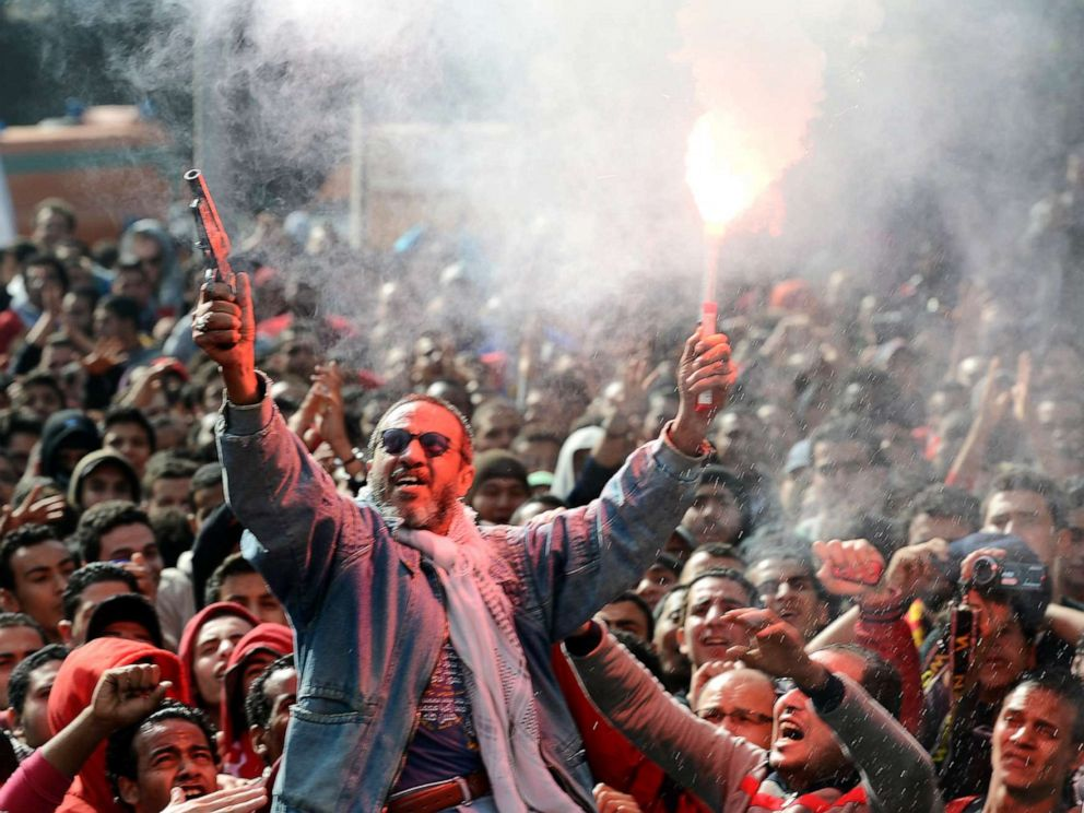 PHOTO: An Egyptian fan of Al-Ahly football club fires celebratory shots in the air and lights a flare as club supporters celebrate outside its headquarters in Cairo, Jan. 26, 2013.