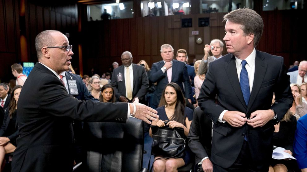 Fred Guttenberg, the father of Jamie Guttenberg who was killed in the Stoneman Douglas High School shooting in Parkland, Fla., left, attempts to shake hands with President Donald Trump's Supreme Court nominee, Brett Kavanaugh, right, as he leaves for a lunch break while appearing before the Senate Judiciary Committee on Capitol Hill in Washington, Sept. 4, 2018.