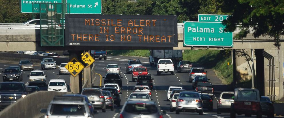 """PHOTO: In this Jan. 13, 2018 photo provided by Civil Beat, cars drive past a highway sign that says """"MISSILE ALERT ERROR THERE IS NO THREAT"""" on the H-1 Freeway in Honolulu."""