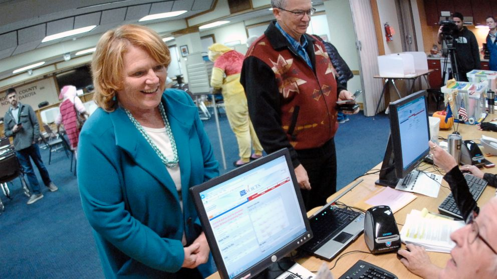 Sen. Heidi Heitkamp talks with a precinct worker before casting her vote at an early voting precinct inside the Morton County Courthouse, Oct. 31, 2018, in Mandan, N.D.