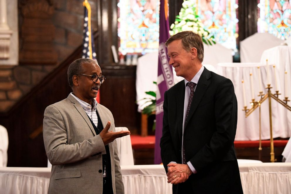 PHOTO: Former Colorado Gov. John Hickenlooper discusses gun control and death penalty issues with Anthony Thompson on April 6, 2019, in Charleston, S.C.