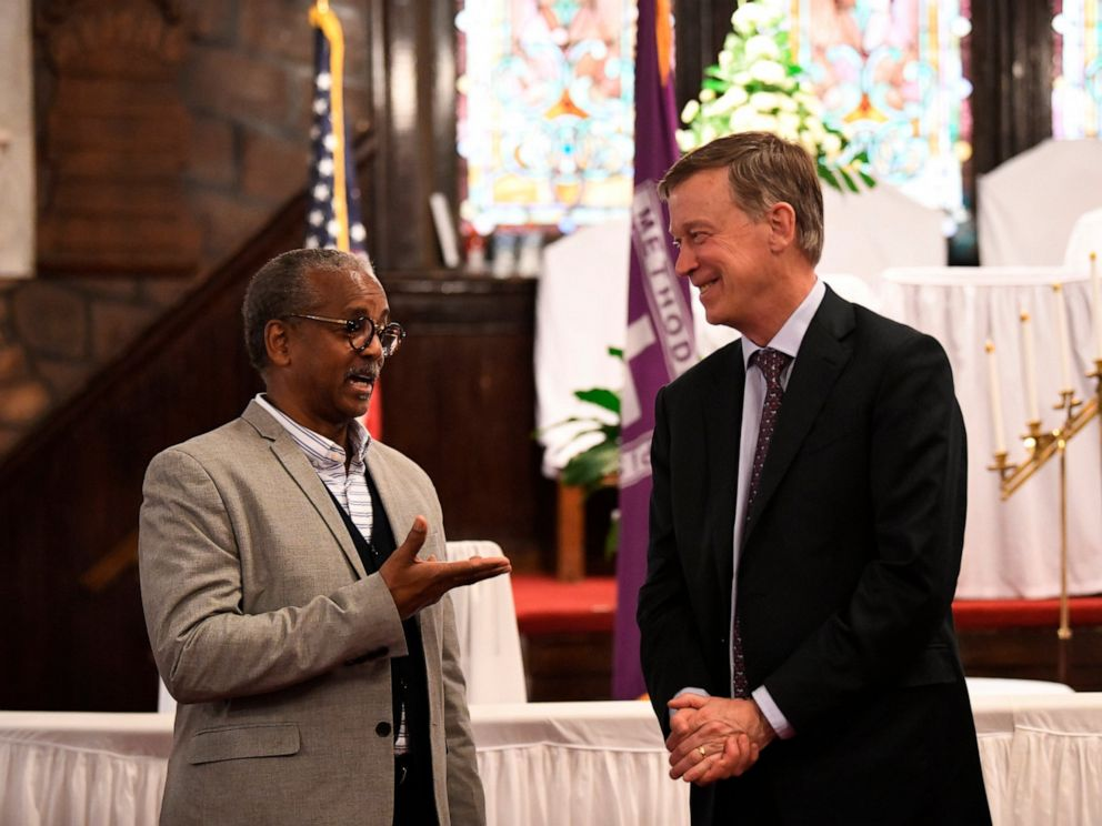 PHOTO: Former Colorado Gov. John Hickenlooper discusses gun control and death penalty issues with Anthony Thompson on Saturday, April 6, 2019, in Charleston, S.C. Thompsons wife was slain in a massacre at a historic black church in South Carolina.