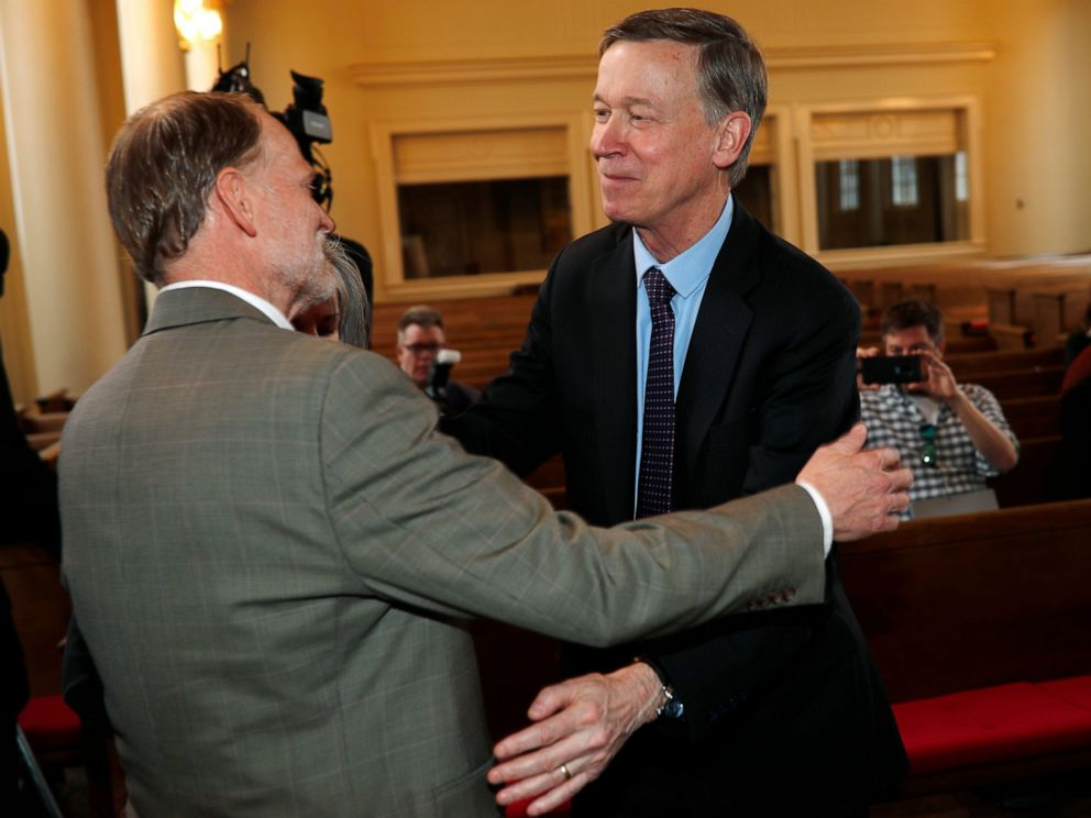 PHOTO: Democratic presidential hopeful John Hickenlooper, right, hugs Michael Davis during a meeting with survivors of victims of mass shootings in Colorado Tuesday, April 16, 2019, in Denver.