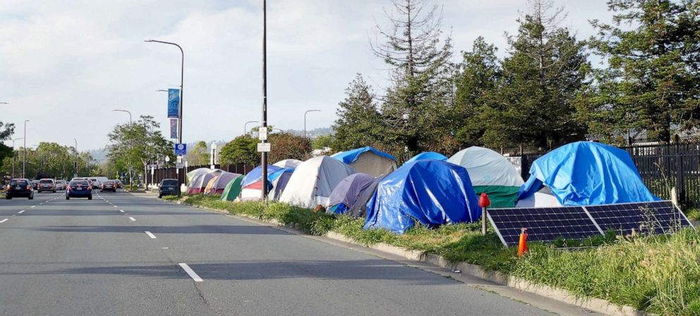 PHOTO: Cars drive past the a homeless encampment along a street in Berkeley, Calif., May 22, 2019.