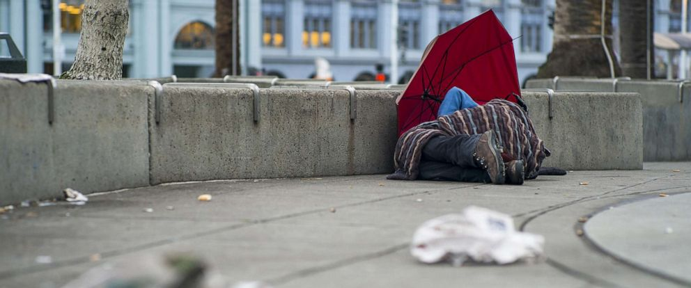PHOTO: A man lies under a blanket by an umbrella in Justin Herman Plaza in San Francisco, Jan. 21, 2016.