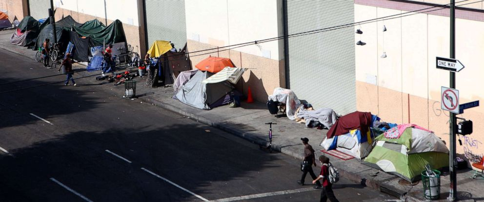 PHOTO: People walk past a homeless tent encampment in Skid Row, Sept. 16, 2019, in Los Angeles.