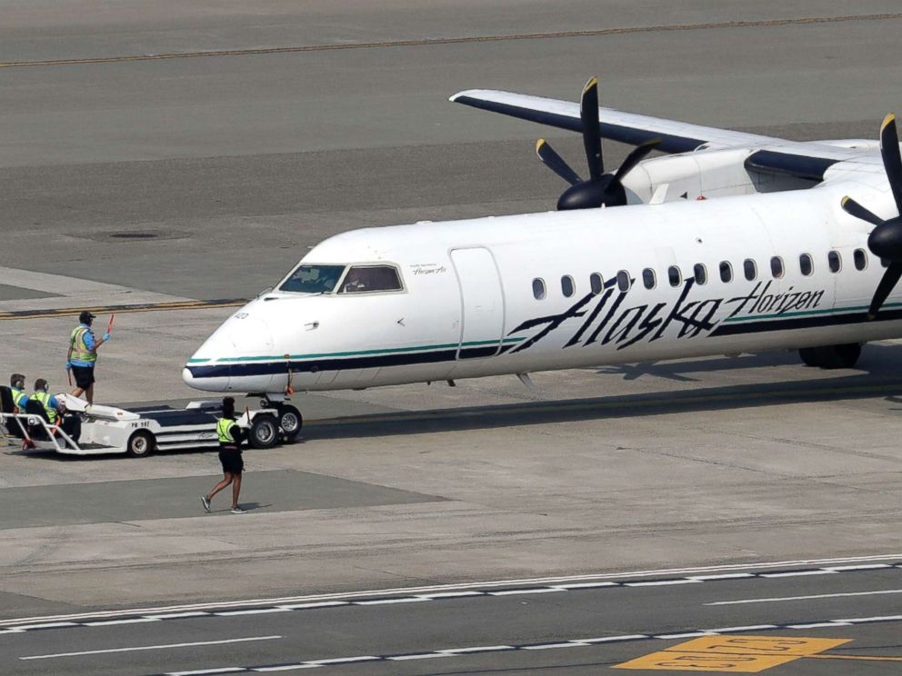 PHOTO: A Horizon Air Q400 turboprop airplane, part of Alaska Air Group, is moved into position by airport workers at Seattle-Tacoma International Airport in SeaTac, Wash., Aug. 13, 2018.