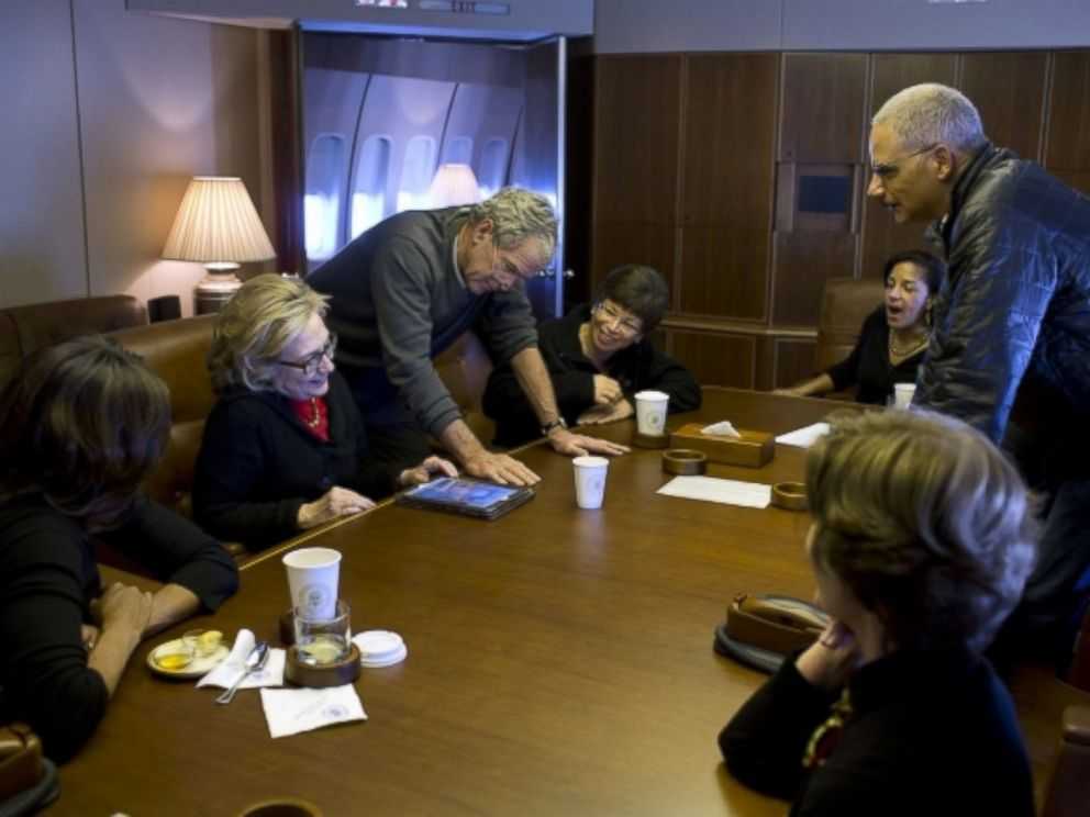 On Air Force One, former President Bush shows photos to First Lady Michelle Obama, former Secretary of State Hillary Clinton, Valerie Jarrett, National Security Advisor Susan E. Rice, Attorney General Eric Holder and former First Lady Laura Bush.