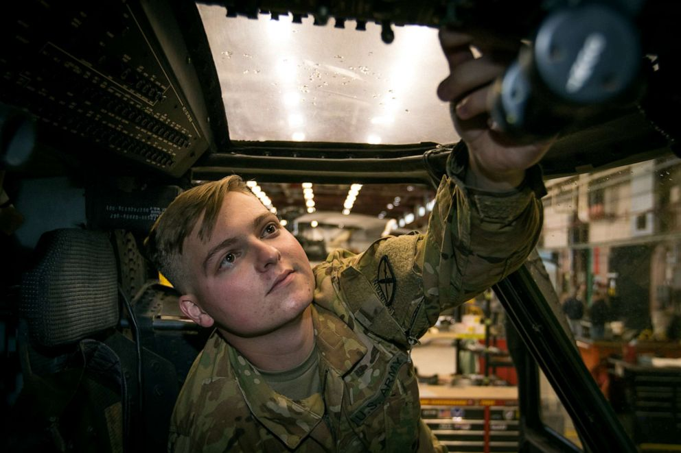 PHOTO: U.S. Army Pvt. Hunter Nines from Company A, 3rd General Support Aviation Battalion, 10th Combat Aviation Brigade inspects cockpit flight controls inside a UH-60M Blackhawk helicopter at Fort Drum, N.Y. on Oct. 4, 2019.