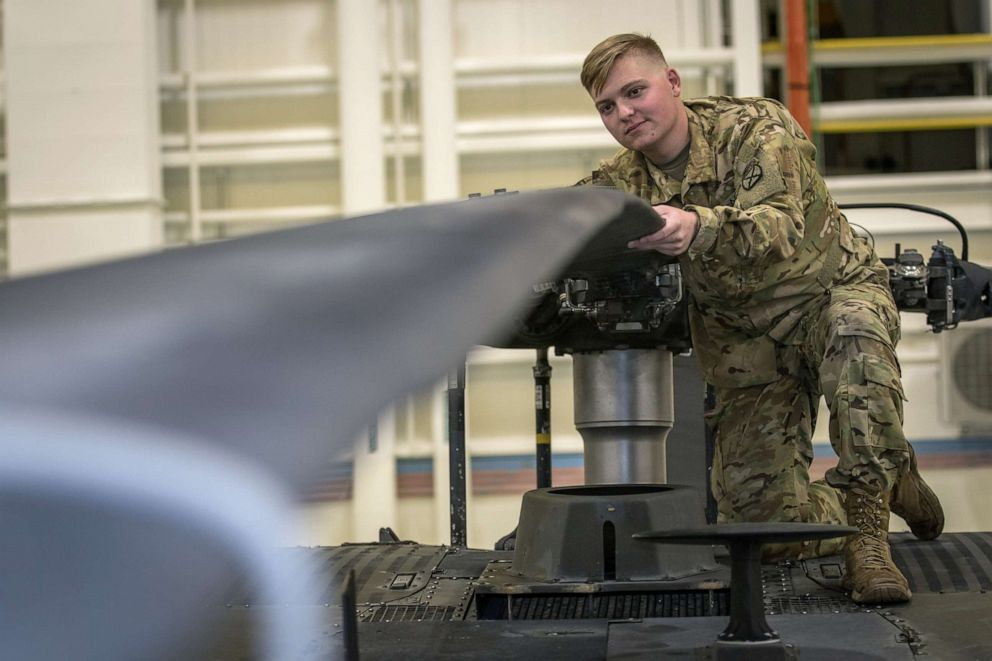 PHOTO: Army Pvt. Hunter Nines inspects UH-60L Blackhawk helicopter main rotor blades for signs of damage during routine helicopter inspections at Fort Drum, N.Y. on Oct, 4, 2019.