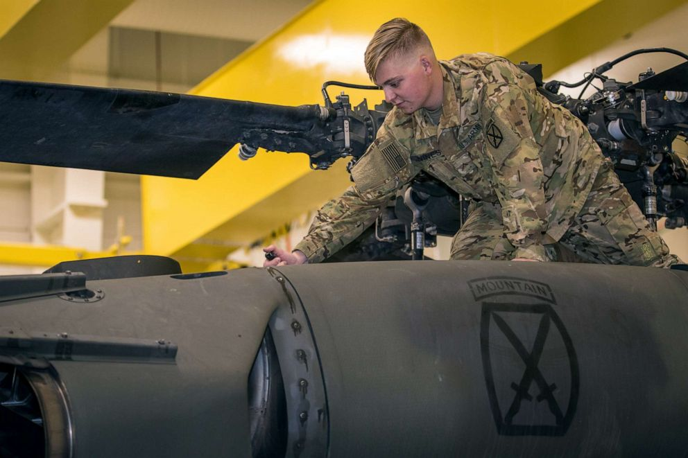 PHOTO: Army Pvt. Hunter Nines opens a UH-60L Blackhawk helicopter engine bay cowling to conduct fuel checks during routine inspections at Fort Drum, N.Y. on Oct. 4, 2019.