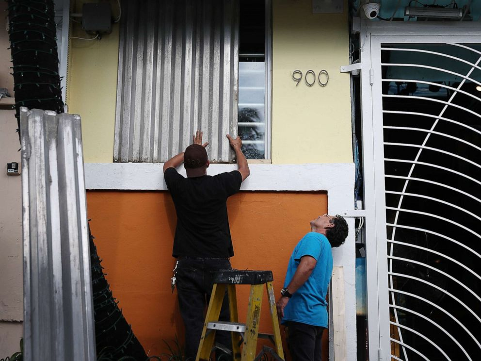 PHOTO: Workers place hurricane shutters over a window as they help prepare a business for the possible arrival of Hurricane Dorian on Aug. 30, 2019, in Miami Beach, Fla.