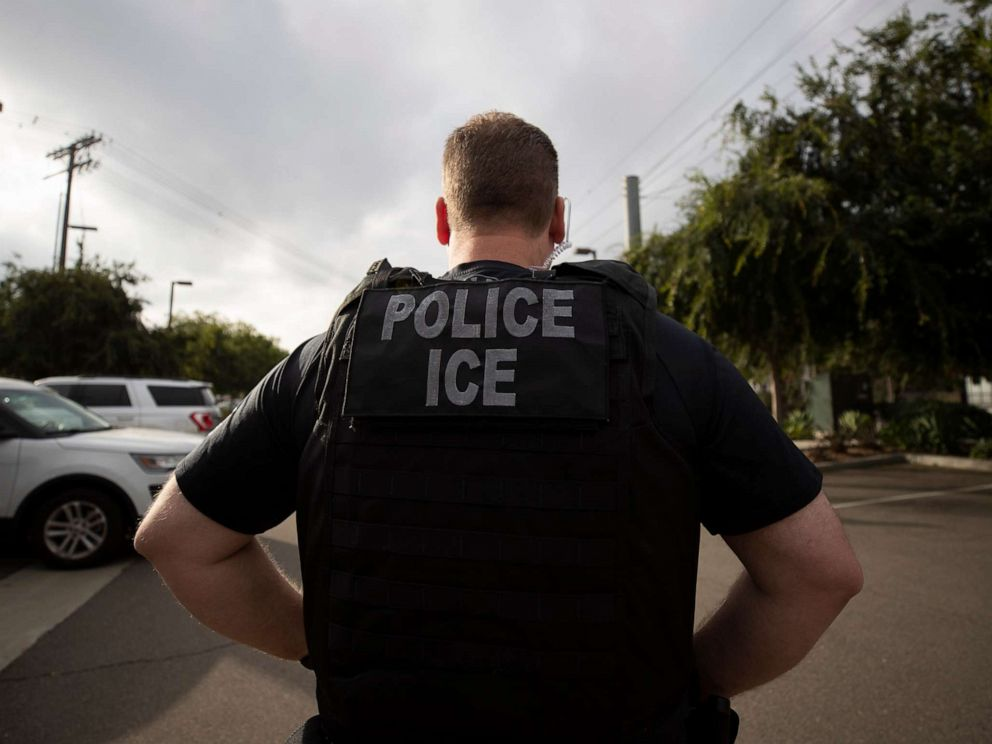 PHOTO: In this July 8, 2019, file photo, a U.S. Immigration and Customs Enforcement (ICE) officer looks on during an operation in Escondido, Calif.
