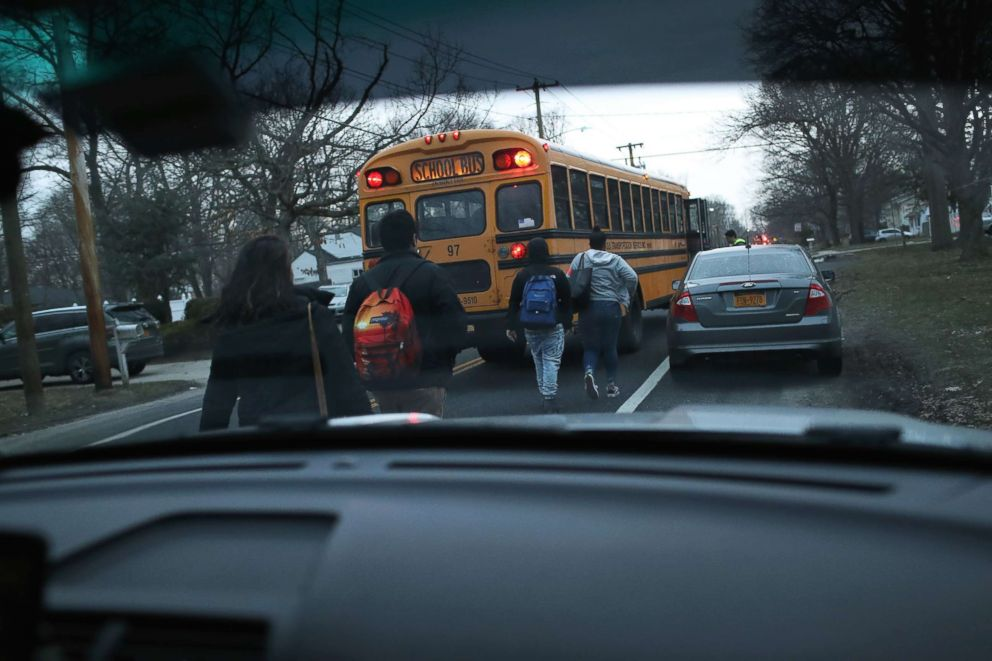PHOTO: Students head to a school bus as Homeland Security Investigations (HSI) ICE agents prepare to arrest a fellow student and suspected MS-13 gang member at a nearby home, March 29, 2018 in Brentwood, New York.