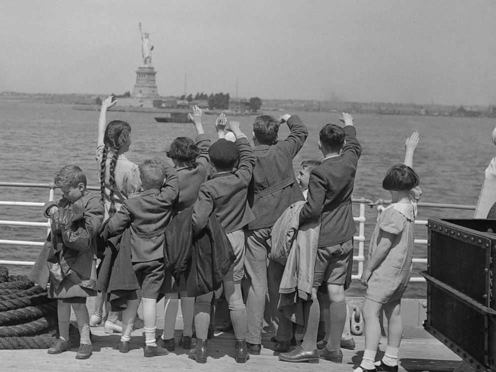 PHOTO: A group of young Austrian immigrants wave to the Statue of Liberty upon their arrival in America aboard the S.S. Harding. The fifty Jewish children, who were greeted by their new adoptive families, were fleeing Nazi persecution in their homeland.