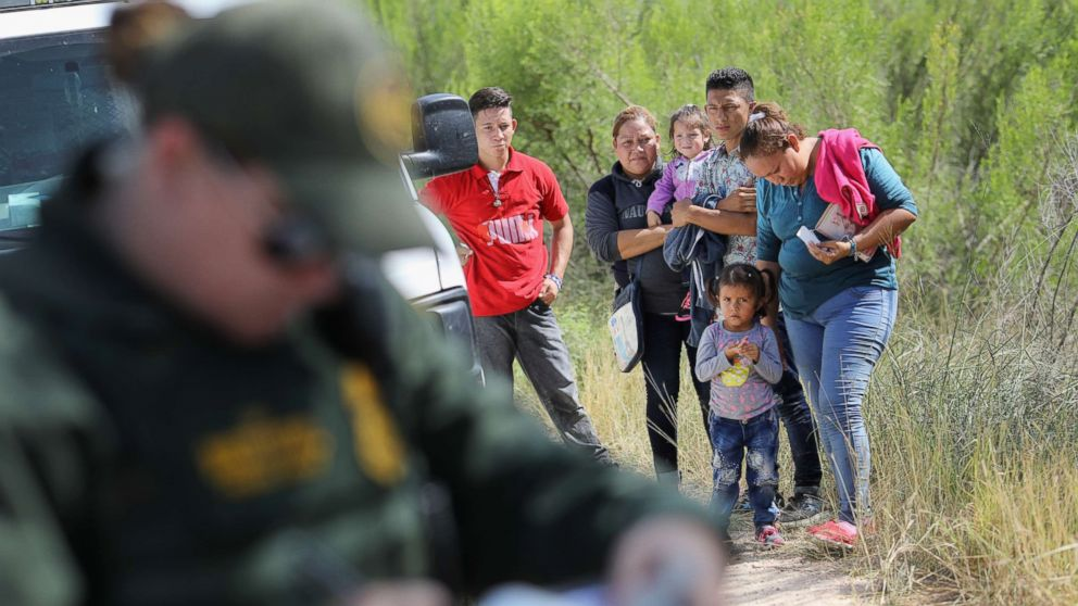 Central American asylum seekers wait as U.S. Border Patrol agents take groups of them into custody, June 12, 2018, near McAllen, Texas.