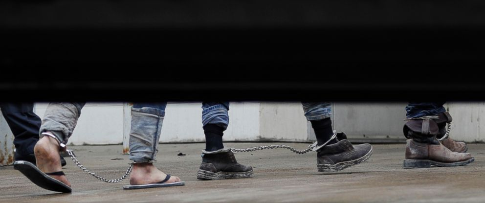 PHOTO: Immigrants in ankle chains disembark from a bus at the Federal Courthouse for hearings, June 22, 2018, in McAllen, Texas.