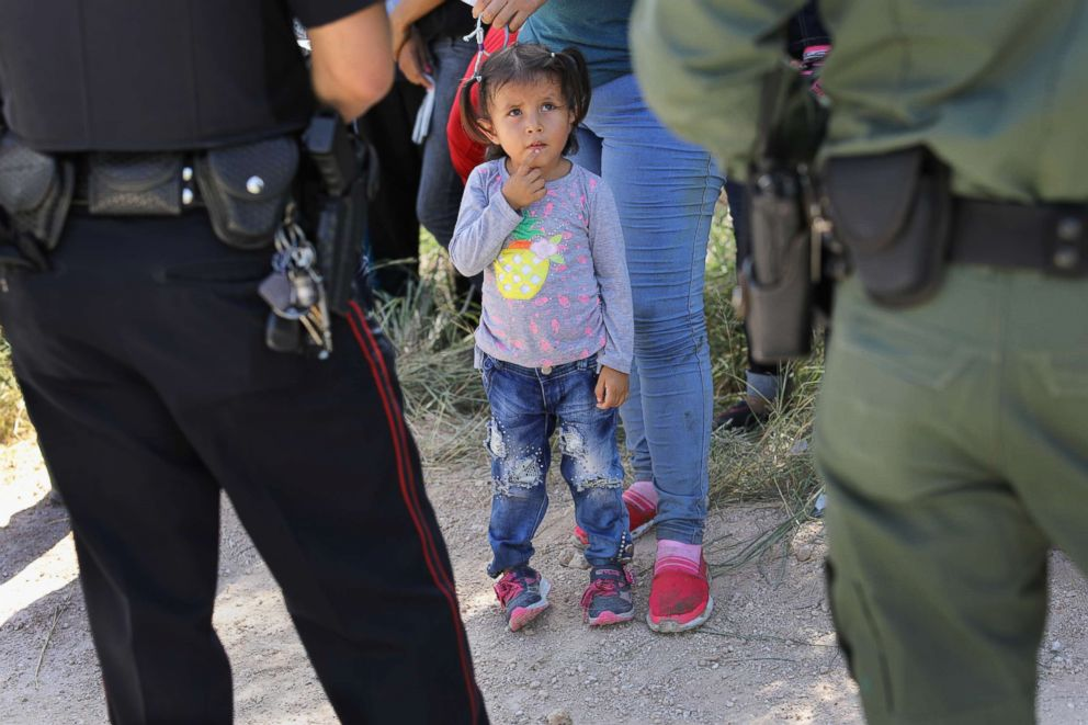 PHOTO: A Mission Police Dept. officer and a U.S. Border Patrol agent watch over a group of Central American asylum seekers before taking them into custody, June 12, 2018, near McAllen, Texas.