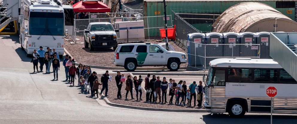 PHOTO: Migrants board buses to take them to shelters after being released from migration detention as construction of a new migrant processing facility is underway at the Customs and Border Protection.