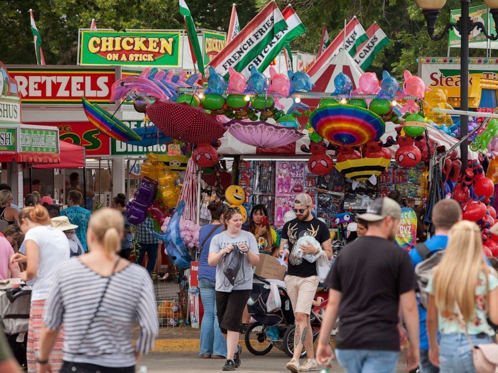 PHOTO: People walk near food kiosks at the Iowa State Fair, Aug. 19, 2018, in Des Moines, Iowa.