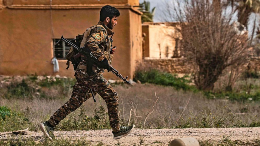 A member of the Syrian Democratic Forces (SDF) runs for cover during shelling on the Islamic State group's last holdout of Baghouz, in the eastern Syrian Deir Ezzor province, March 3, 2019. Kurdish-led forces backed by US warplanes rained artillery fire and air strikes on besieged and outgunned jihadists making a desperate last stand in a Syrian village.