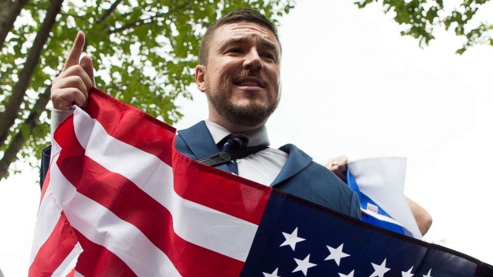 """Jason Kessler speaks to members of the news media while holding a U.S. national flag in Lafayette Park across the street from the White House, during the """"Unite the Right"""" rally, Aug. 12, 2018."""