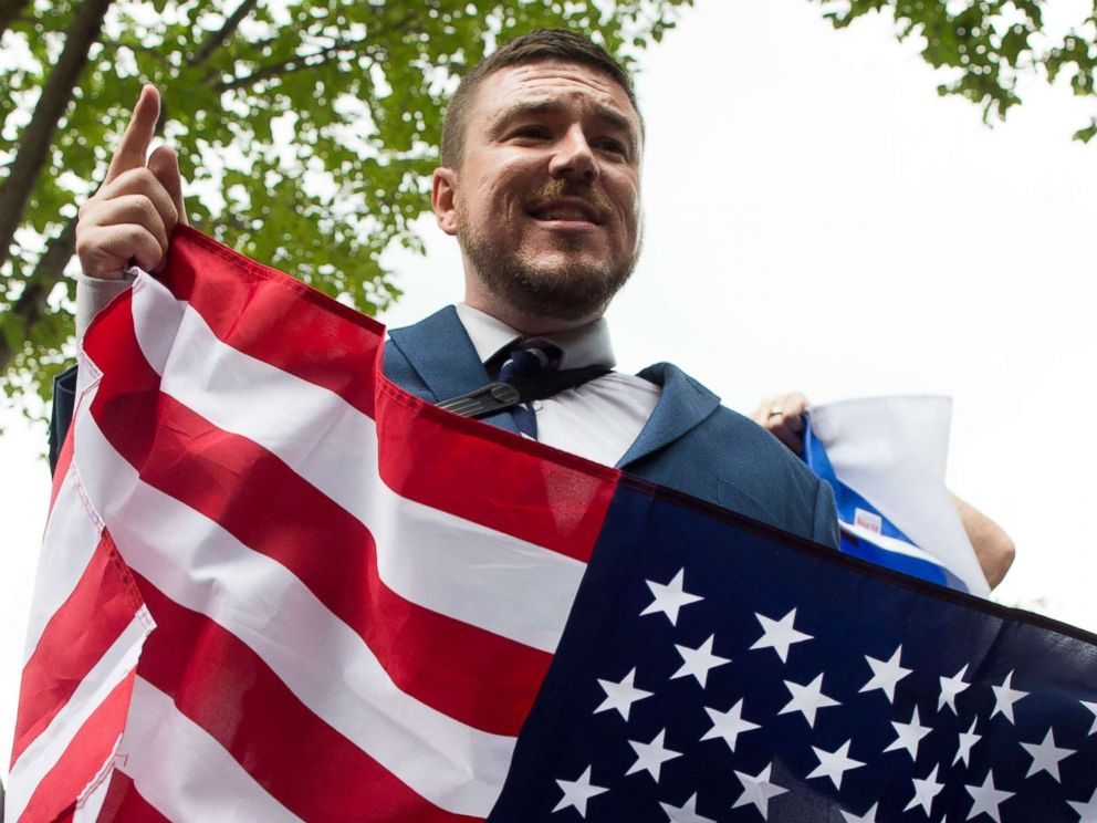 PHOTO: Jason Kessler speaks to members of the news media while holding a U.S. national flag in Lafayette Park across the street from the White House, during the Unite the Right rally, Aug. 12, 2018.