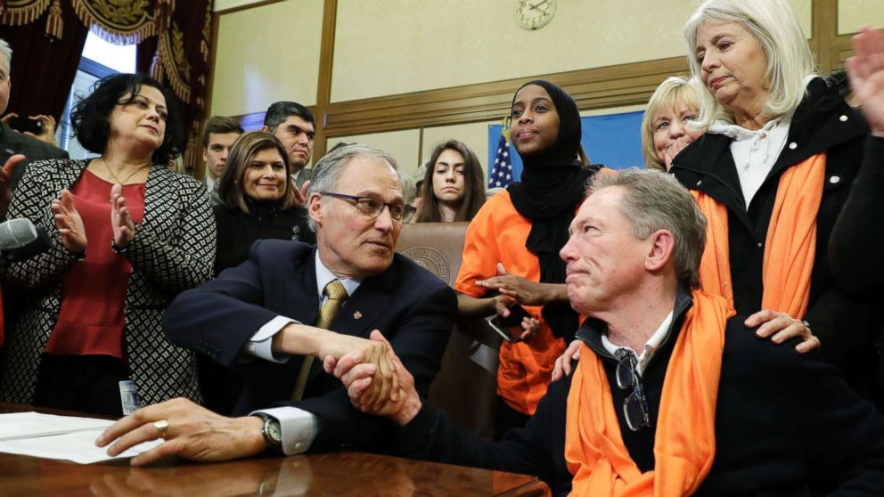Washington Gov. Jay Inslee, center, shakes hands with the father of a shooting victim after Inslee signed a measure into law that bans the sale and possession of bump stocks, March 6, 2018.
