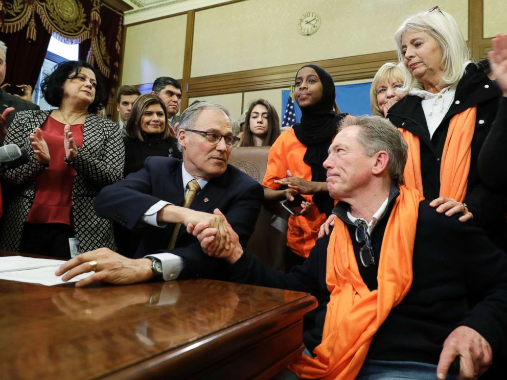 PHOTO: Washington Gov. Jay Inslee, center, shakes hands with the father of a shooting victim after Inslee signed a measure into law that bans the sale and possession of bump stocks, March 6, 2018.