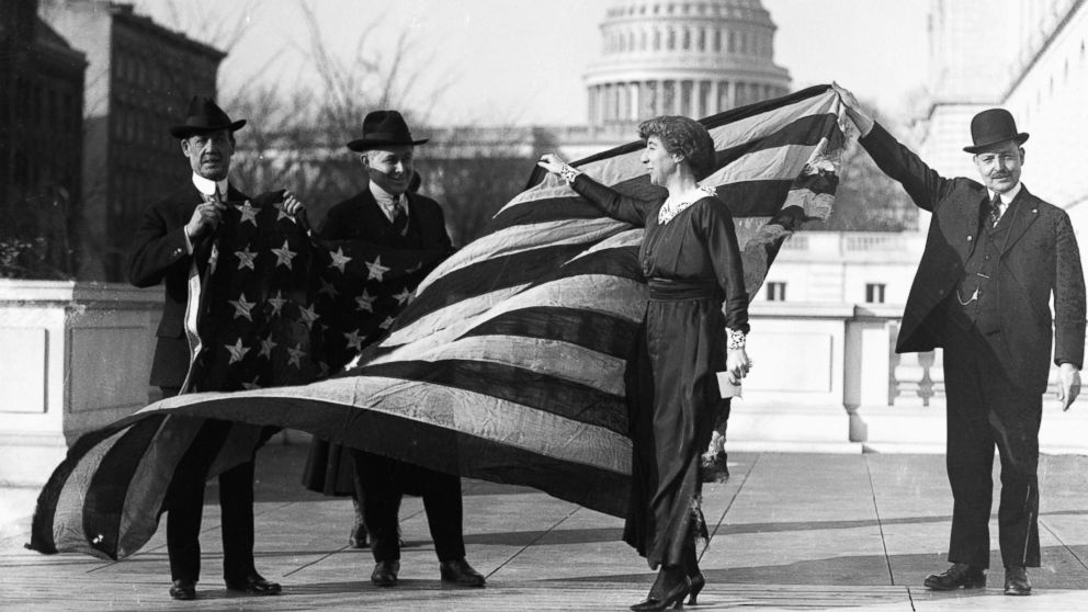 Congresswoman Jeannette Rankin is presented with the flag that flew at the House of Representatives during the passage of the suffrage amendment, circa Jan. 21, 1918.