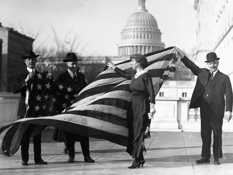 PHOTO: Congresswoman Jeannette Rankin is presented with the flag that flew at the House of Representatives during the passage of the suffrage amendment, circa Jan. 21, 1918.