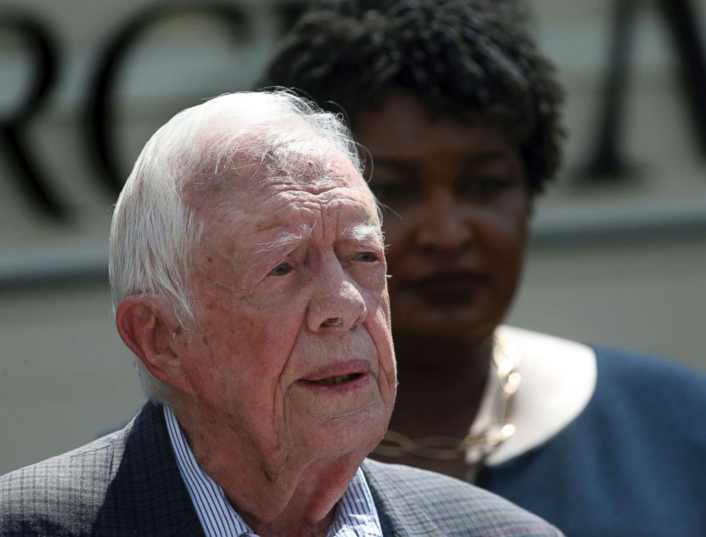 Former President Jimmy Carter speaks as Democratic gubernatorial candidate Stacey Abrams listens on during a news conference to announce her rural health care plan in Plains, Ga., Sept. 18, 2018.
