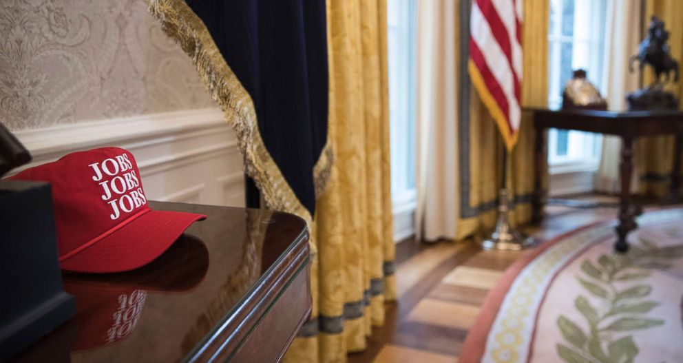 PHOTO: A red hat with Jobs, Jobs, Jobs printed on it rests on a table in the Oval Office, Jan. 31, 2018.