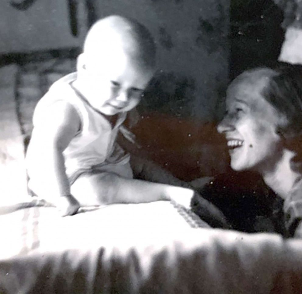 PHOTO: Former Gov. John Hickenlooper sits on a bed while his mom Anne watches. Undated.