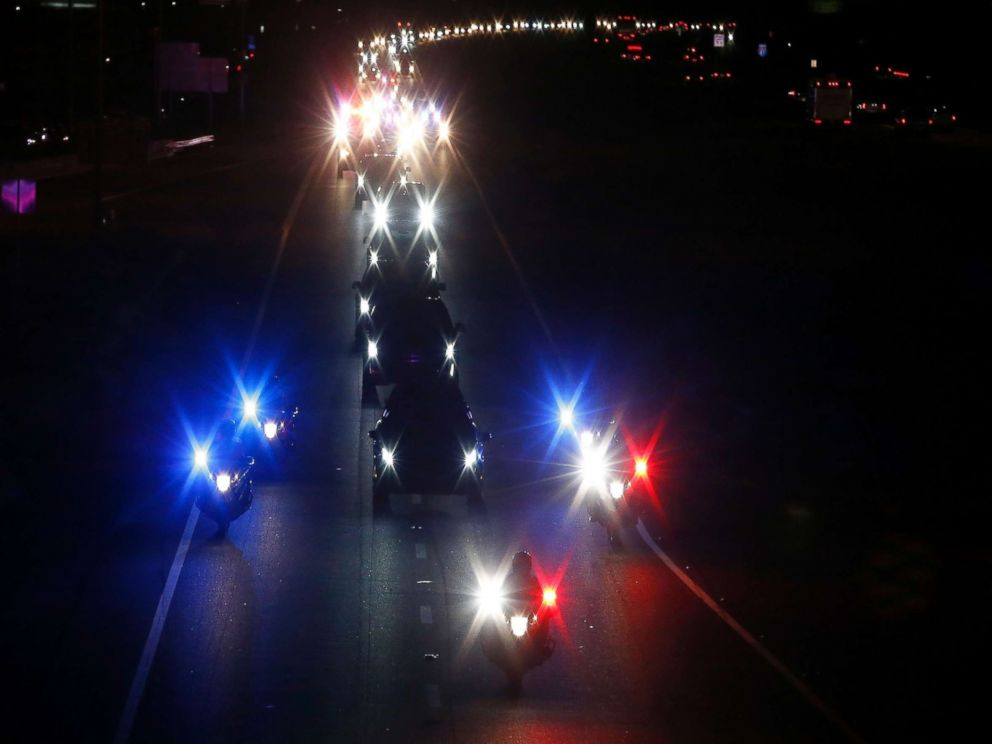 PHOTO: With a police escort, a long procession follows the hearse carrying the late Arizona Sen. John McCain, along Interstate 17 en route to Phoenix, Aug. 25, 2018, in Anthem, Ariz.