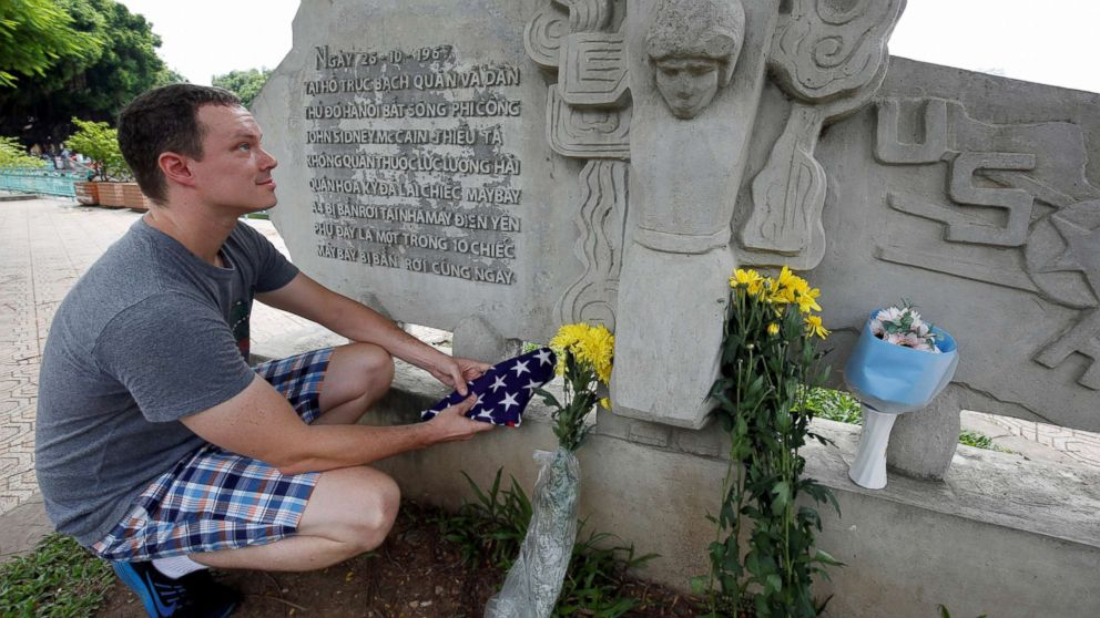 English teacher Derek Davis from the U.S. places an American flag and flowers in memory of the late Senator John McCain at the McCain Memorial in Hanoi, Vietnam, Aug. 26, 2018.